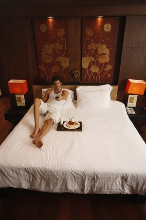 Man watching television with breakfast on bed photo