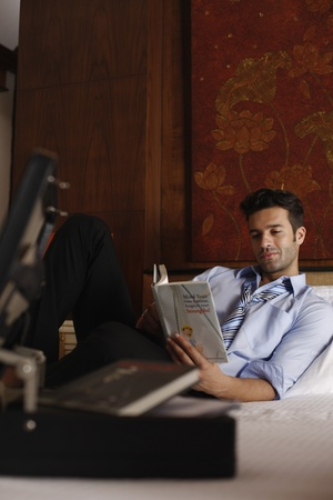 southeastern european descent: Businessman reading book on bed