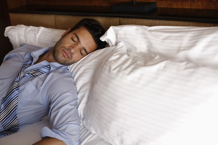 southeastern european descent: Businessman sleeping on bed