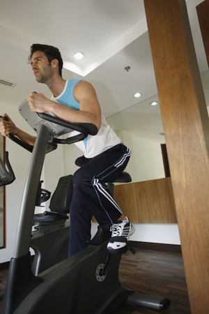 Man on exercise bike at gym photo