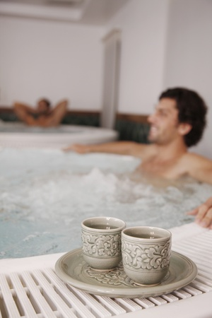 southeastern european descent: Men relaxing in hot tub, focus on tea cups in the foreground