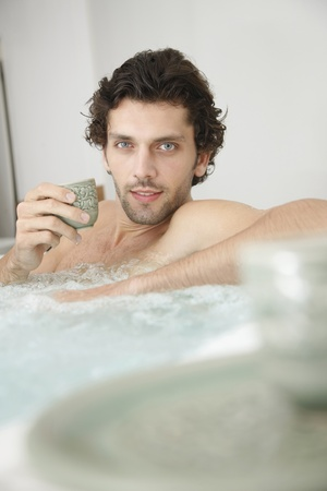 Man relaxing in hot tub enjoying a cup of hot tea photo