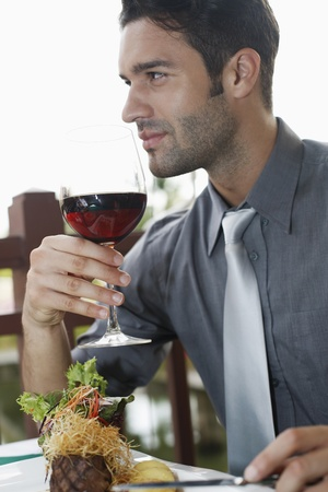 southeastern european descent: Businessman holding wineglass Stock Photo