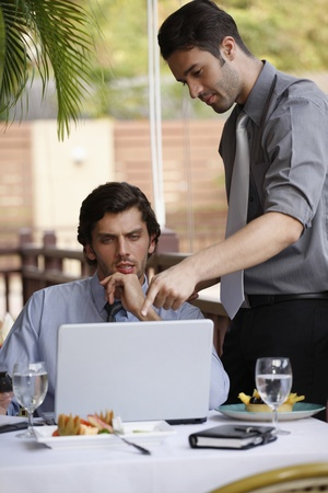 Businessmen discussing work over lunch at restaurant photo
