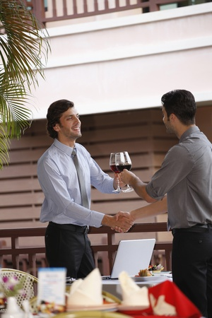 southeastern european descent: Businessmen shaking hands and toasting red wine Stock Photo