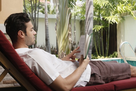 southeastern european descent: Man reading book on lounge chair