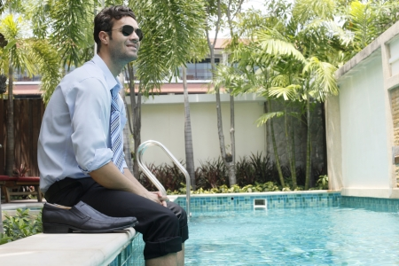 southeastern european descent: Businessman wearing sunglasses with feet in swimming pool