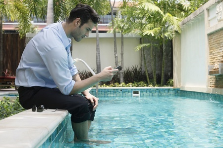 southeastern european descent: Businessman with feet in swimming pool, text messaging