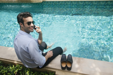 southeastern european descent: Businessman talking on the phone with feet in swimming pool