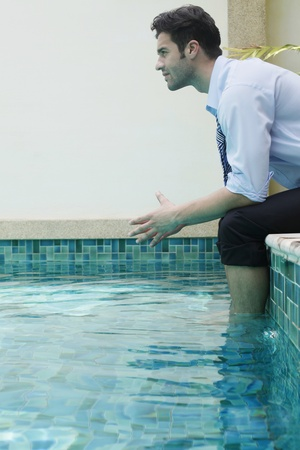 Businessman sitting with feet in swimming pool, contemplating photo
