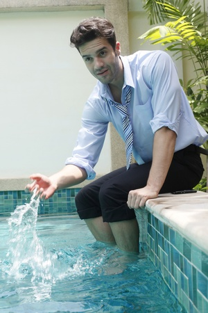 southeastern european descent: Businessman with feet in swimming pool, splashing water