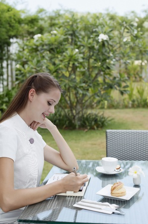 Woman writing in organizer while having breakfast outdoors photo