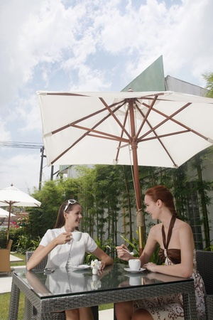 Women having coffee together outdoors photo