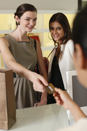 Woman handing credit card to cashier while her friend looks on photo