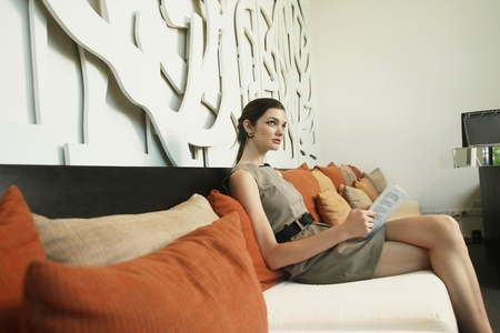 legs crossed at knee: Woman reading book on sofa Stock Photo