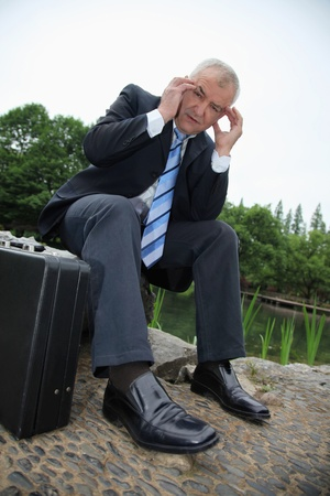 italian ethnicity: Businessman sitting on a rock with hands on his head