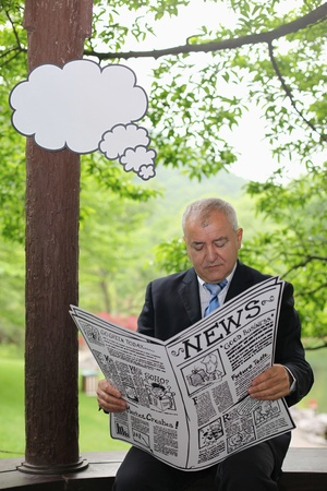 Businessman reading newspaper with thinking bubble above him Stock Photo - 13378452