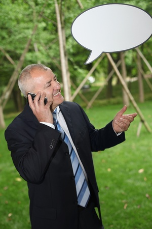 Businessman talking on the phone with speech bubble above him photo