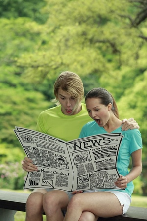 Man and woman reading newspaper Stock Photo - 13378454
