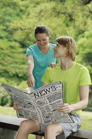 Man and woman reading newspaper together Stock Photo - 13378582