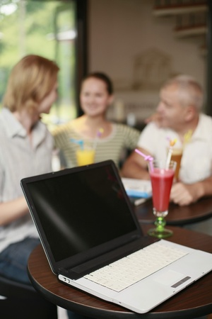 italian ethnicity: Laptop on the table, men and woman in the background Stock Photo