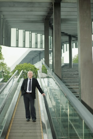Businessman on escalator, hand in pocket photo