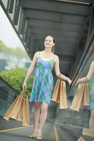 Woman with shopping bags standing on escalator photo