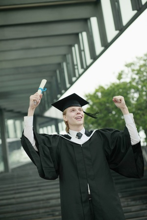 jubilating: Man in graduation gown holding up his scroll Stock Photo