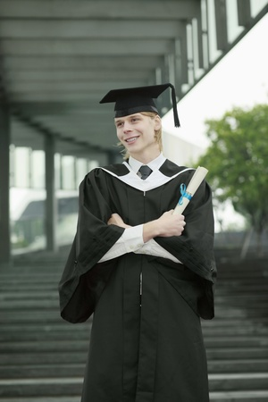 Man in graduation gown holding scroll photo