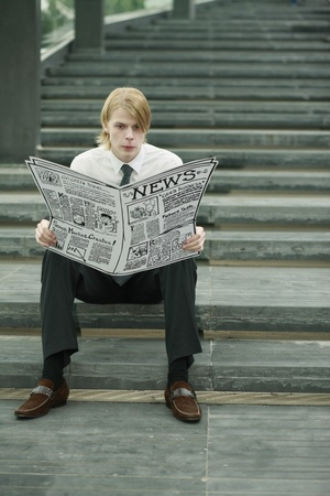Businessman reading newspaper on the stairs photo