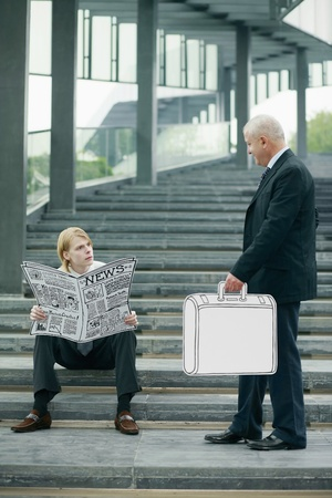 Businessman reading newspaper on the stairs, another businessman carrying briefcase Stock Photo - 13378137