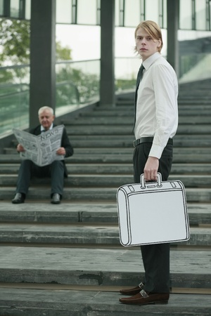 Businessman reading newspaper on the stairs, another businessman carrying briefcase photo