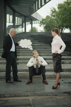 Businessman holding thinking bubble above another businessmans head, businesswoman watching photo