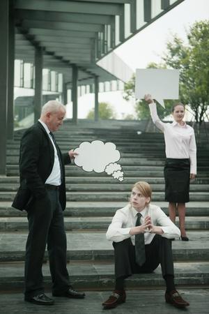 Businessman holding thinking bubble above another businessman's head, businesswoman holding speech bubble photo