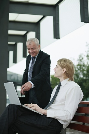 Businessman using laptop, another businessman pointing at the screen photo