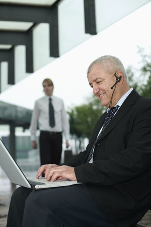 Businessman with telephone headset using laptop photo