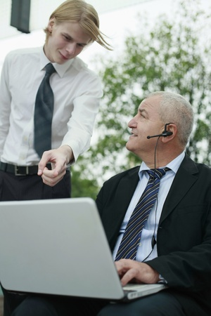 Businessman with telephone headset using laptop, another businessman pointing at the screen photo