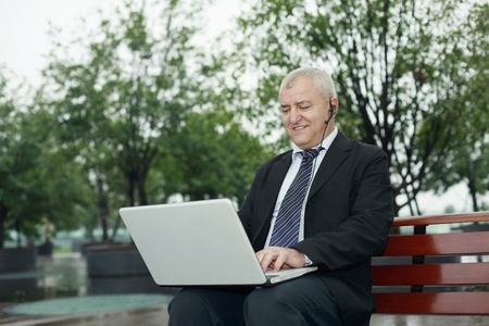 Businessman with telephone headset using laptop Stock Photo - 13377958