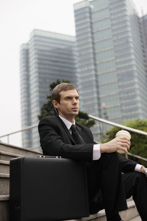 Businessman sitting on stairs holding a cup of coffee photo