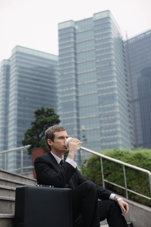 Businessman sitting on stairs drinking a cup of coffee photo