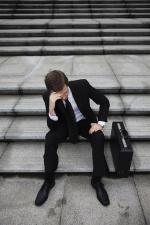 business wear:  Businessman sitting on stairs looking depressed Stock Photo