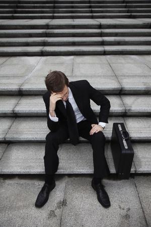 Businessman sitting on stairs looking depressed Standard-Bild