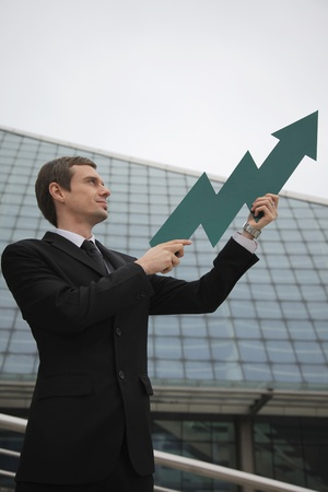 Businessman holding an arrow pointing up Stock Photo - 13377824