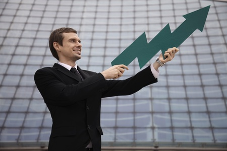 Businessman holding an arrow pointing up Stock Photo - 13377890