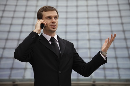 Businessman talking on mobile phone with hand gesture photo