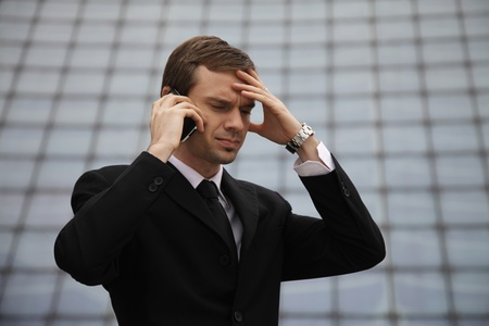 Businessman talking on the phone with hand on forehead photo