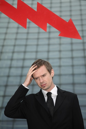 Businessman with hand on forehead and arrow pointing down in the background Stock Photo - 13377878