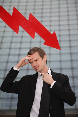 Businessman with hand on forehead and arrow pointing down in the background Stock Photo - 13377884