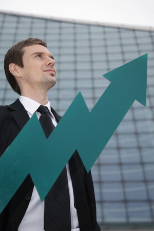 Businessman smiling, arrow pointing up in front of him