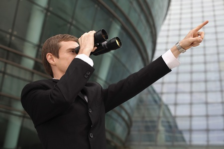 Businessman looking through binoculars and pointing ahead Stock Photo